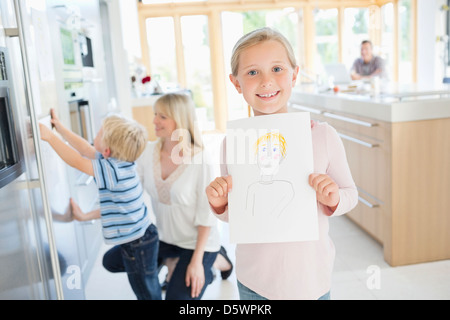 Girl showing off drawing in kitchen - Stock Photo
