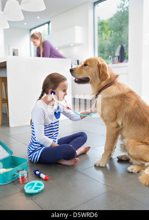 Girl playing doctor with dog in kitchen - Stock Photo