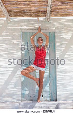 Woman practicing yoga in doorway - Stock Photo