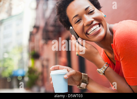 Woman on cell phone on city street - Stock Photo