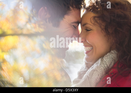 Smiling couple touching noses outdoors - Stock Photo