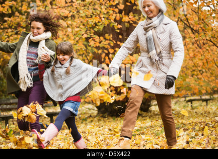 Three generations of women playing in autumn leaves - Stockfoto