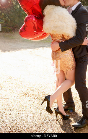 Young Couple Kissing Holding Heart Shaped Balloon - Stockfoto