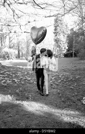 Young Couple Kissing in Park Holding Heart Shaped Balloons - Stock Photo