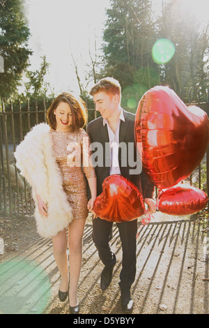 Young Couple in Park Holding Heart Shaped Balloons - Stock Photo