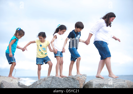 Family Walking on Rocks by Sea Holding Hands - Stock Photo