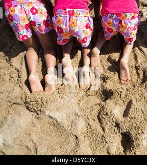 Back View of Girls in Matching Outfit Kneeling on Sand, Cropped - Stock Photo