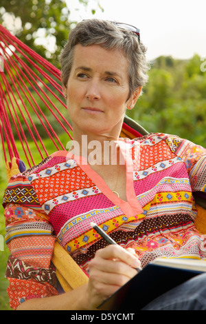 Woman on Hammock Writing - Stock Photo