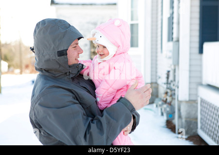 Man Carrying Baby Girl in her Arms - Stock Photo