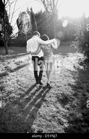 Couple in Park Holding Heart Shaped Balloon, Back View - Stock Photo