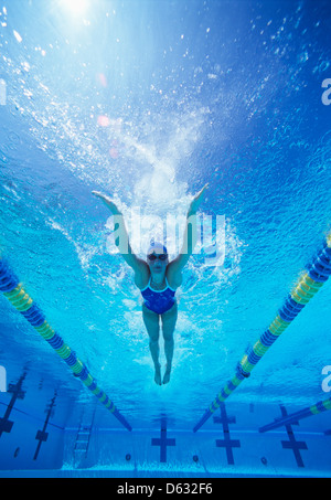 Full length of female swimmer in United States swimsuit swimming in pool - Stock Photo