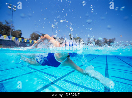 Female swimmer in United States swimsuit swimming in pool - Stock Photo