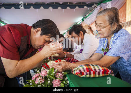 Bangkok, Thailand. April 13, 2013. A man makes merit by washing the hands of an elderly woman in scented water during - Stock Photo