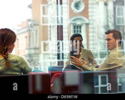 Business people talking in office lobby - Stock Photo