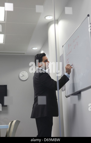 Businessman writing on whiteboard - Stock Photo