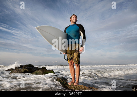 Surfer standing on rocks on beach - Stock Photo