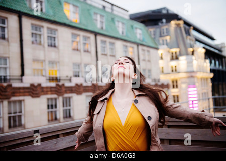 Businesswoman standing on urban rooftop - Stock Photo