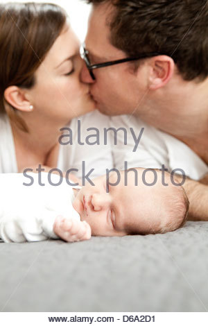 Parents kissing on bed with infant boy - Stock Photo