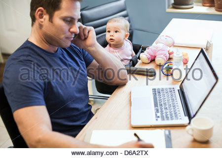 Baby girl sitting with father at work - Stock Photo