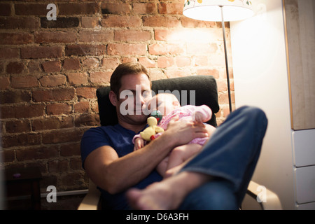 Father holding baby daughter in armchair - Stock Photo