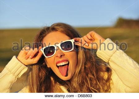 Woman in sunglasses in rural field - Stock Photo