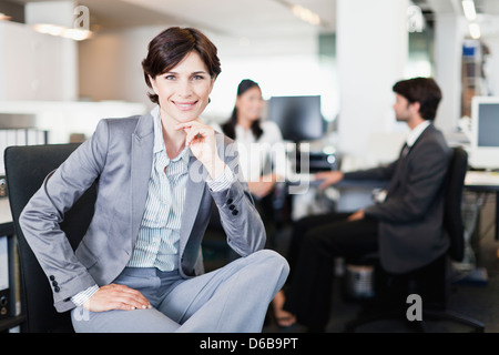 Businesswoman smiling in office - Stock Photo