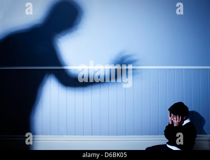 Shadow looming over frightened boy - Stock Photo