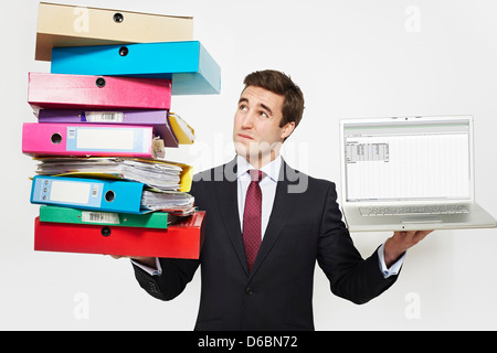 Businessman with stacks of folders and laptop - Stockfoto