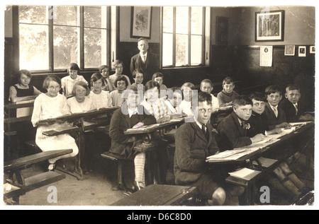 Postcard of a teacher with junior girls & boys sitting at their desks, with open books in classroom, 1940's, U.K. - Stock Photo