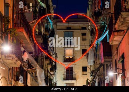 Red heart shaped neon light in Raval neighbourhood, Barcelona, Catalonia, Spain - Stock Photo