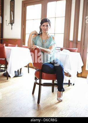 Girl sitting on red chair inside restaurant - Stock Photo