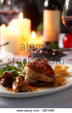 Roast pheasant with bacon strips, sausages and salad for Christmas dinner - Stock Photo