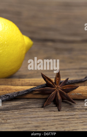 Cinnamon sticks, star anise and vanilla pod and a lemon in the background on a rustic wooden board - Stock Photo