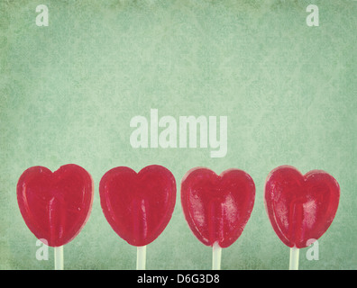 Row of red lollipop hearts on green vintage background with copy space - Stock Photo
