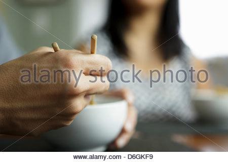 Close up of man using chopsticks - Stockfoto