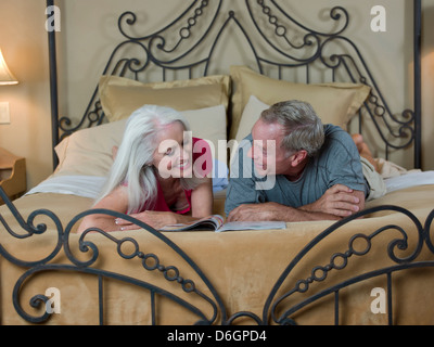 Older couple reading on bed - Stock Photo