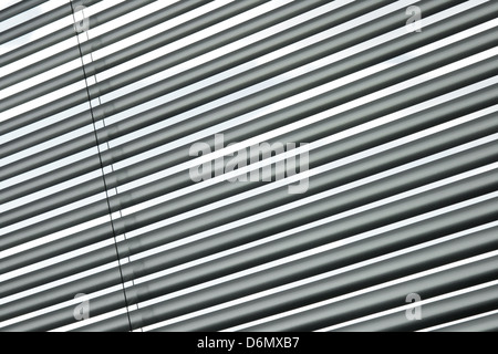 Semi-closed metallic blinds on a window, diagonal striped pattern. - Stock Photo