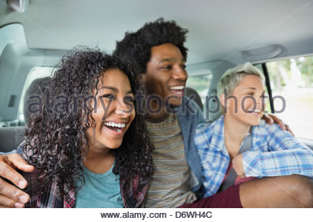 Happy young man with arms around female friends sitting in truck - Stock Photo