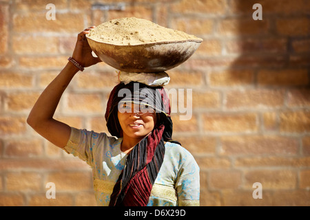 Street scene - portrait of a india hindu smiling woman carrying a basket on her head, Jaisalmer, India - Stock Photo