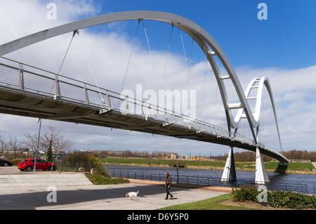 Man walking dog beneath the Infinity Bridge Stockton-on-Tees north east England UK - Stock Photo