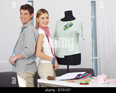 Two happy fashion designer standing with dress form in their studio - Stock Photo