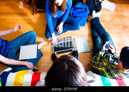 overhead view of a group of teens on the floor working on a project using various means and technologies.  multi - Stockfoto