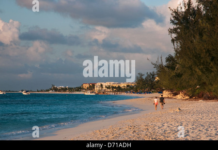 Couple walking along Grace Bay in Providenciales, Turks and Caicos at sunset - Stockfoto
