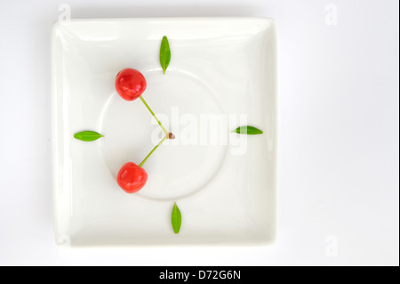 cherry fruit clock isolated on plate - Stock Photo