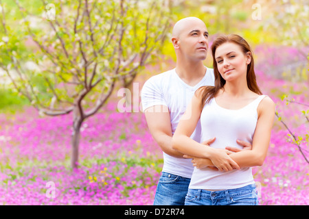 Happy young family embracing on purple floral field, having fun outdoors, first love, spring nature, affection concept - Stock Photo