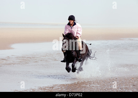 A young woman riding her pet pony on the beach, Holkham Beach, Norfolk UK - Stockfoto