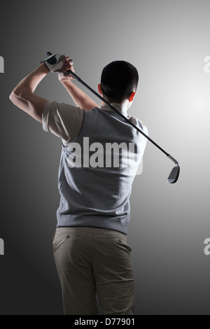 Young golf player swinging, rear view - Stock Photo