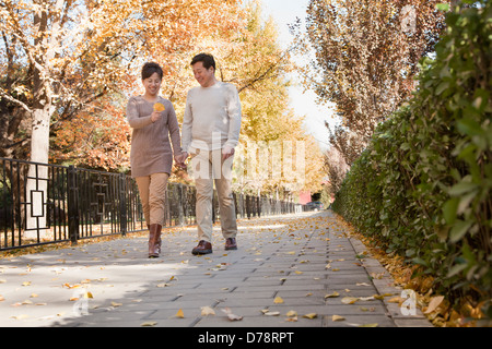 Mature Couple Talking a Walk in the Park - Stock Photo