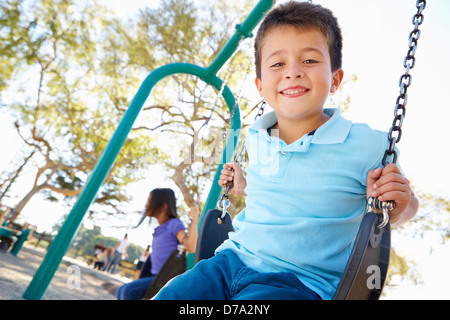 Boy And Girl Playing On Swing In Park - Stock Photo