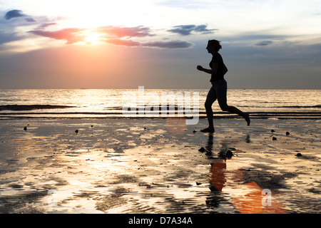 Silhouette of a young woman jogger at sunset on seashore. - Stock Photo